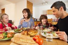 Familia que come el almuerzo junto en cocina Foto de archivo libre de regalías