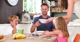 Familia que come el desayuno en cocina junto almacen de video