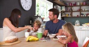 Familia que come el desayuno en cocina junto almacen de metraje de vídeo