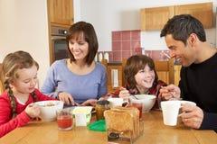 Familia que come el desayuno junto en cocina Foto de archivo libre de regalías