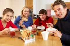 Familia que come el desayuno junto en cocina Fotos de archivo