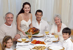 Familia que come el pavo en una cena Foto de archivo