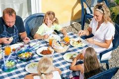 Familia que come en el jardín Fotografía de archivo libre de regalías
