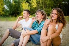 Familia que come la barra de chocolate como presentan para la imagen Fotografía de archivo