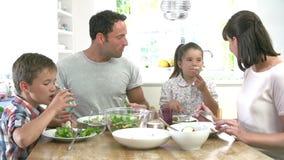 Familia que come la comida alrededor de la tabla de cocina junto metrajes