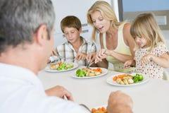 Familia que come la comida de A, mealtime junto Imágenes de archivo libres de regalías