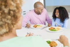 Familia que come la comida de A, mealtime junto Fotos de archivo libres de regalías