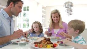Familia que come la comida en casa junto almacen de video
