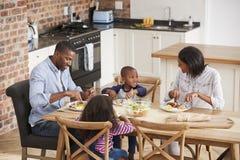 Familia que come la comida en cocina abierta del plan junto imágenes de archivo libres de regalías
