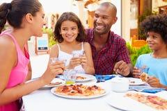 Familia que come la comida en el restaurante al aire libre junto fotografía de archivo