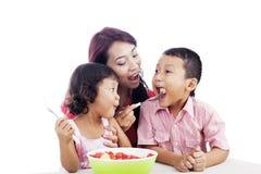 Familia que come la ensalada de fruta Fotos de archivo