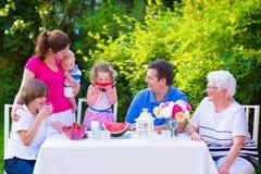 Familia que come la fruta en el jardín Imagen de archivo