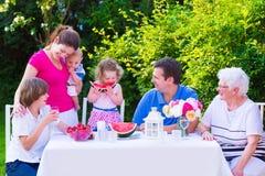Familia que come la fruta en el jardín Imagen de archivo libre de regalías