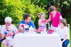 Familia que come la fruta en el jardín Imágenes de archivo libres de regalías