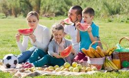 Familia que come la sandía en la comida campestre Fotos de archivo libres de regalías