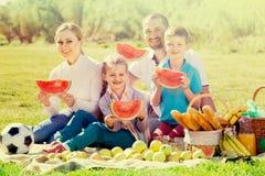 Familia que come la sandía en la comida campestre Imagenes de archivo