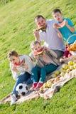 Familia que come la sandía en la comida campestre Imagen de archivo libre de regalías