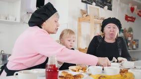 Familia que come las crepes en la cocina Una niña que come el plátano almacen de metraje de vídeo