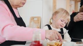 Familia que come las crepes Una niña que come el plátano almacen de metraje de vídeo