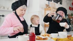 Familia que come las crepes y que bebe té Una niña que come el plátano metrajes