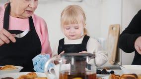 Familia que come las crepes y que bebe té Una niña come la zarzamora almacen de video