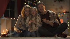 Familia que come las galletas dulces en el piso, el árbol de navidad y las luces chispeando, víspera almacen de metraje de vídeo