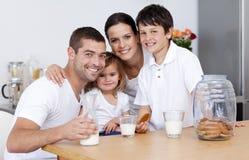 Familia que come las galletas y la leche de consumo