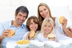 Familia que come las hamburguesas Foto de archivo libre de regalías