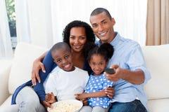Familia que come las palomitas y que ve la TV Foto de archivo