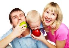 Familia que come manzanas Foto de archivo