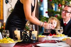 Familia que come salchichas de la cena de la Navidad Imagenes de archivo