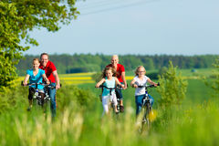 Familia que completa un ciclo al aire libre en verano Imagen de archivo libre de regalías