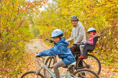 Familia que completa un ciclo al aire libre, otoño de oro en parque Imagenes de archivo