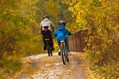 Familia que completa un ciclo al aire libre, parque del otoño Fotografía de archivo