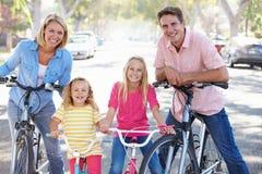 Familia que completa un ciclo en la calle suburbana Imagenes de archivo