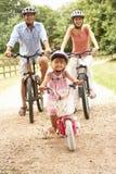Familia que completa un ciclo en la seguridad que desgasta Helme del campo fotos de archivo libres de regalías