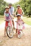 Familia que completa un ciclo en la seguridad que desgasta Helme del campo Foto de archivo libre de regalías