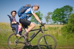 Familia que completa un ciclo en verano Foto de archivo libre de regalías