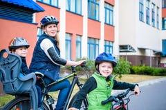 Familia que completa un ciclo, madre con la bici feliz del montar a caballo del niño al aire libre Fotos de archivo libres de regalías