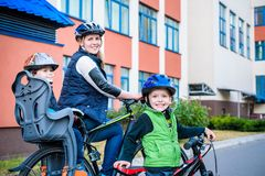 Familia que completa un ciclo, madre con la bici feliz del montar a caballo del niño al aire libre Fotografía de archivo