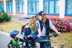Familia que completa un ciclo, madre con la bici feliz del montar a caballo del niño al aire libre Imágenes de archivo libres de regalías