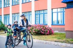 Familia que completa un ciclo, madre con la bici feliz del montar a caballo del niño al aire libre Imagen de archivo libre de regalías