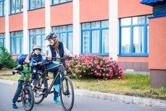 Familia que completa un ciclo, madre con la bici feliz del montar a caballo del niño al aire libre Imagen de archivo