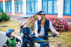 Familia que completa un ciclo, madre con la bici feliz del montar a caballo del niño al aire libre Foto de archivo
