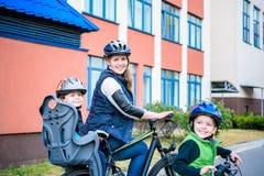 Familia que completa un ciclo, madre con la bici feliz del montar a caballo del niño al aire libre Fotografía de archivo libre de regalías