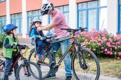Familia que completa un ciclo, padre con la bici feliz del montar a caballo del niño al aire libre Fotos de archivo libres de regalías