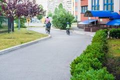 Familia que completa un ciclo, padre con la bici feliz del montar a caballo del niño al aire libre Fotos de archivo