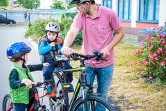 Familia que completa un ciclo, padre con la bici feliz del montar a caballo del niño al aire libre Imágenes de archivo libres de regalías