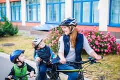 Familia que completa un ciclo, padre con la bici feliz del montar a caballo del niño al aire libre Fotografía de archivo libre de regalías