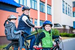 Familia que completa un ciclo, padre con la bici feliz del montar a caballo del niño al aire libre Imagen de archivo